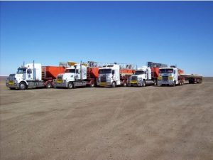 four trucks on an open plain loaded with barges
