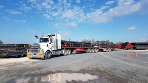 Double road train loaded with pipes, standing in pipe yard