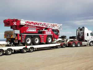 truck on side of road with large crane vehicle loaded onto heavy haulage open trailer