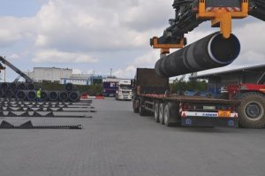 Single open trailer truck being loaded with large pipe by a crane