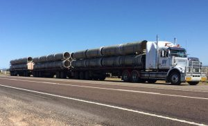 Triple road train loaded with large pipes