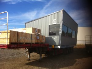 Temporary housing building loaded onto flat top trailer