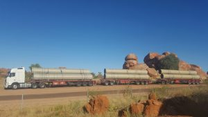 Triple road train truck with large pipes parked at the Devils Marbles