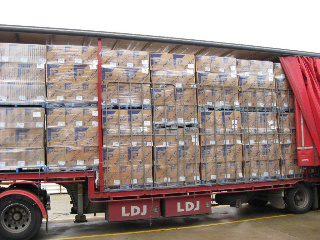 tautliner trailer with curtains opened, revealing load of wrapped, palletised boxes
