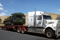 truck with defence vehicle loaded onto flat top trailer