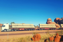 triple road train loaded with large pipes in front of Devil's Marbles landmark in the Northern Territory