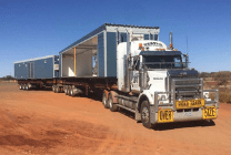 road train truck with two portable accommodation modules loaded onto trailers