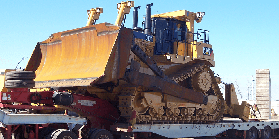 Large construction machine loaded onto a trailer
